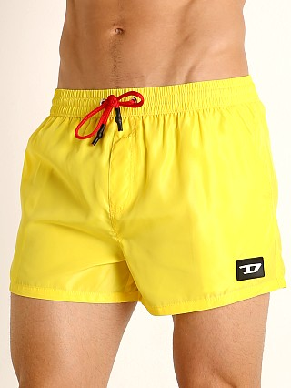 Model in blazing yellow Diesel Caybay Swim Shorts