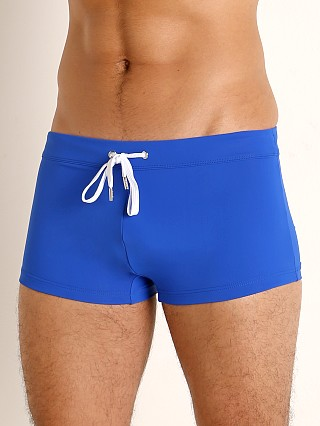 Model in blacklight blue 2xist Cabo Sliq Swim Trunk