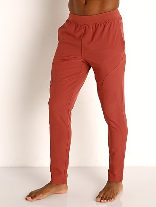 Model in cinna red/black Under Armour Flex Woven Tapered Pants