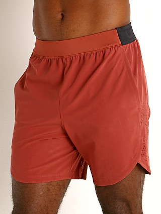 Model in cinna red/metallic solder Under Armour Stretch Woven Shorts