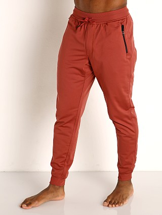 Model in cinna red Under Armour Sportstyle Tricot Pant